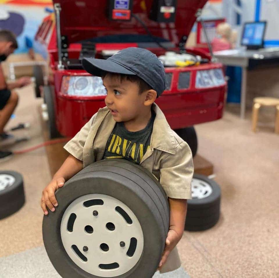 Little boy holding toy tire.
